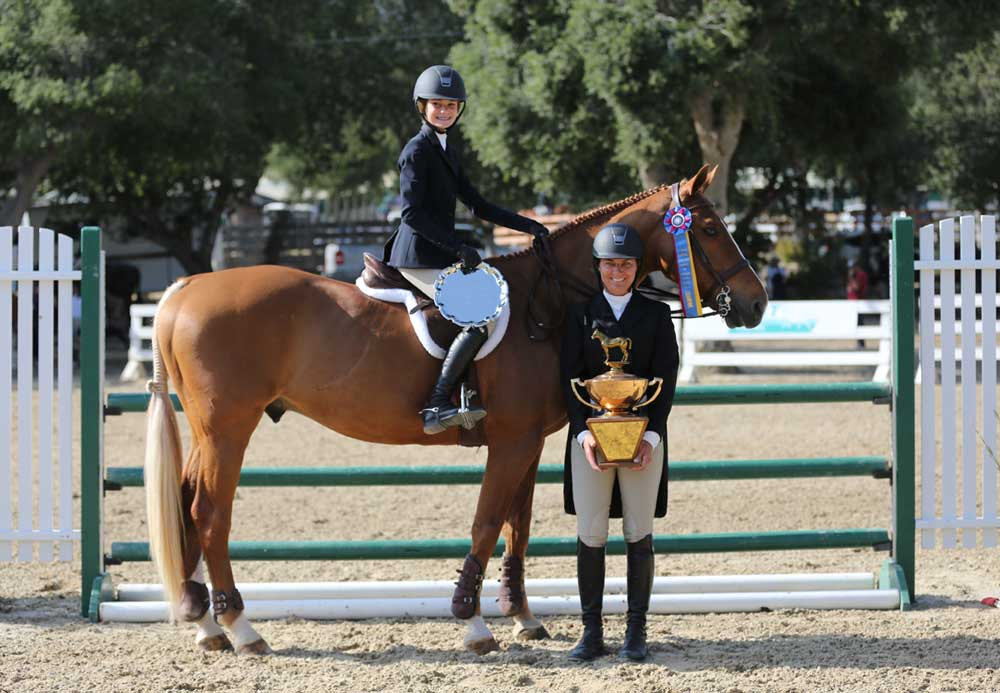 Andie Aviv collects the coveted tricolor ribbon that means best in show honors .